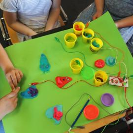 Hands of children, working on a green desk table with colorful plasticine (first steps in easy making with makey makey)